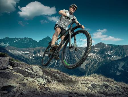 ciclista: Hombre en casco y gafas de permanecer en la bicicleta bajo el cielo con nubes.