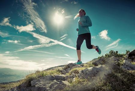 accion: Mujer corriendo en montañas bajo la luz del sol. Foto de archivo