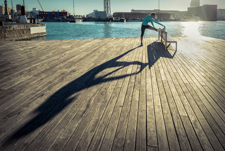 20 29: Woman do exercise after running on the wooden pier under sunlight