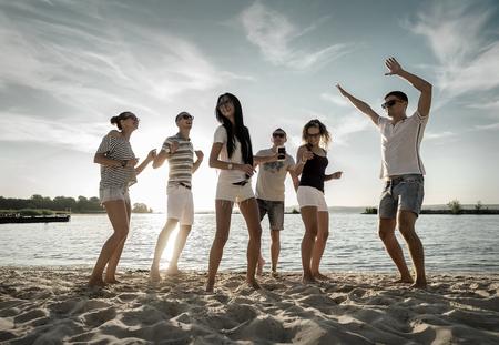 Amigos de baile divertido en la playa bajo la luz del sol puesta de sol.