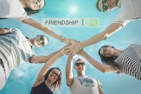 circulo de personas: Grupo de amigos en la playa bajo la luz solar. Foto de archivo