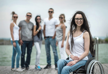 20 29: Young people on the pier with them disabled friend. Stock Photo