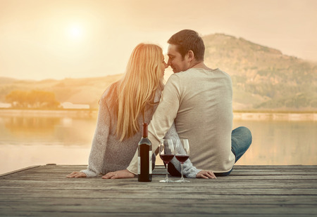 happy anniversary: Romantic Couple sitting on the pier with red wine. Stock Photo