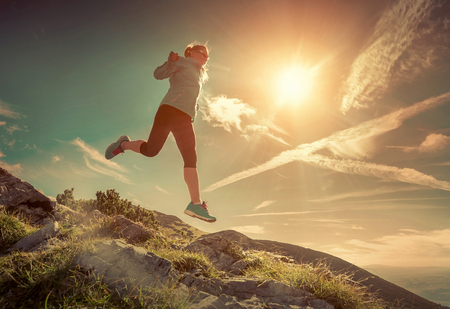 Female running in mountains under sunlight. Stock Photo