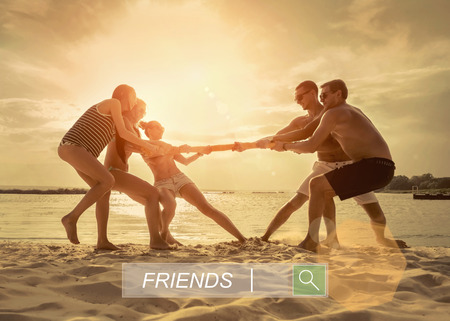 25 29: Friends funny tug of war on the beach under sunset sunlight.