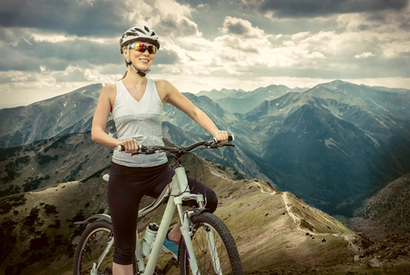 cycling: Beautiful woman in helmet and glasses stay on the bicycle around mountains.