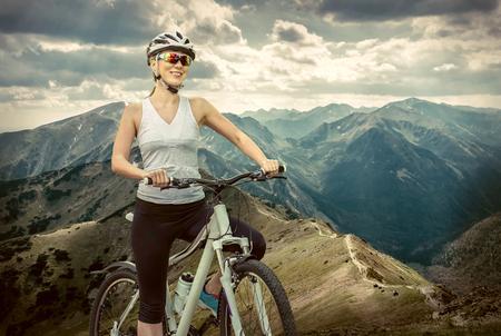 ciclismo: Mujer hermosa en casco y gafas de permanecer en la bicicleta por las montañas.