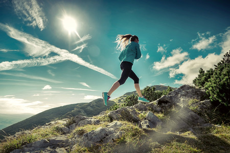 Female running in mountains under sunlight. Standard-Bild