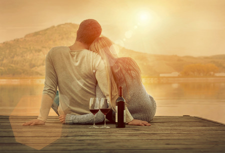 lake sunset: Romantic Couple sitting on the pier with red wine. Stock Photo