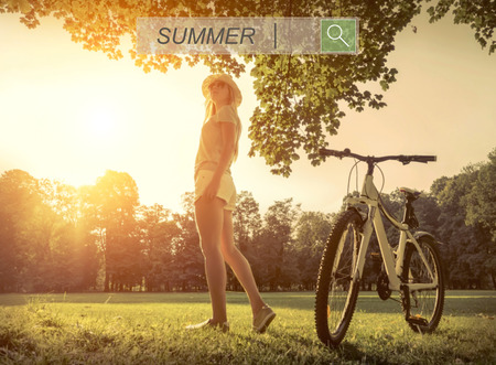 day light: Woman under sun light at day near her bicycle in the park Stock Photo