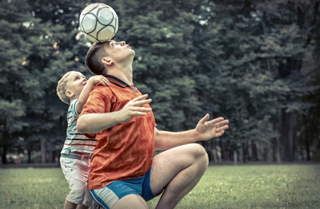father and son: Father and son playing football in park at sunny day