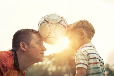 play: Padre e hijo jugando al fútbol en el parque en día soleado