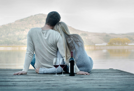 two hands: Romantic Couple sitting on the pier with red wine. Stock Photo