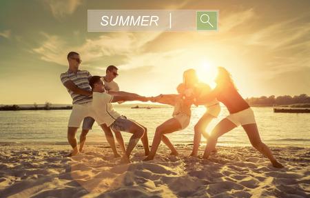 Vrienden grappig touwtrekken op het strand onder zonsondergang zonlicht.