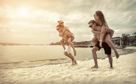 gente corriendo: Amigos de la diversión en la playa bajo la luz del sol puesta de sol.