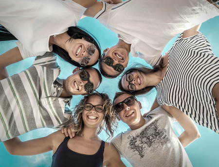 huddling: Group of friends on the beach under sunlight. Stock Photo