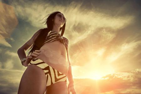 sunlight sky: Woman stay on the beach under sky with sunlight.