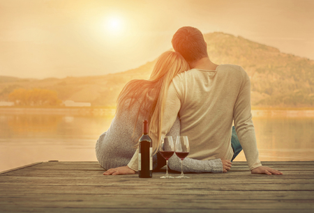 happy couple: Romantic Couple sitting on the pier with red wine. Stock Photo