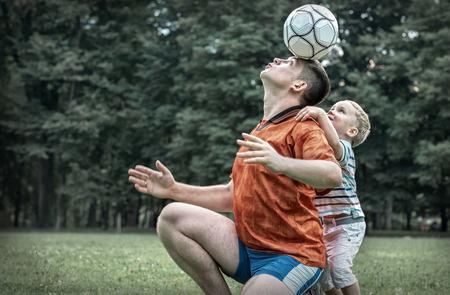 jugando futbol: Padre e hijo jugando al fútbol en el parque en día soleado