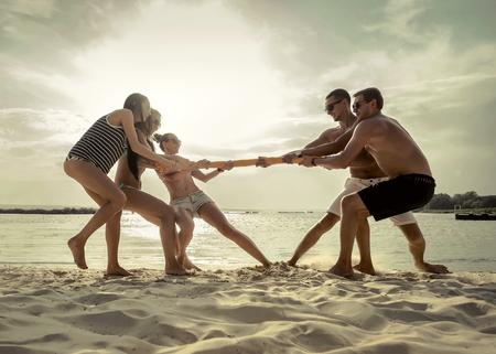 Friends funny tug of war on the beach under sunset sunlight.