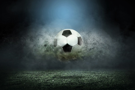 Moviendo el balón de fútbol alrededor de las gotas del chapoteo en el campo del estadio. Foto de archivo - 56564621