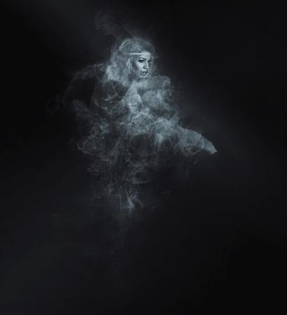 smoke effect: Dancer from smoke on the dark background