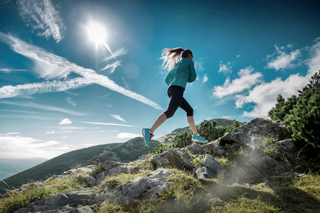 Female running in mountains under sunlight. Stok Fotoğraf