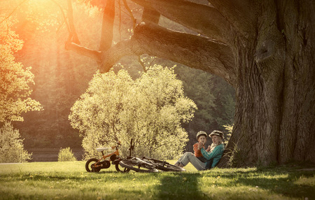 madre figlio: Madre e figlio con loro biciclette nel parco sotto la luce del sole. Archivio Fotografico