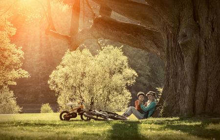 bicicleta: Madre e hijo con ellos bicicletas en el parque bajo la luz del sol.