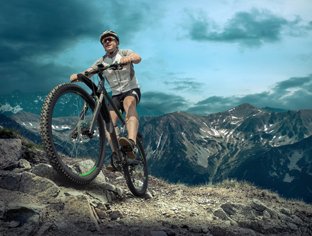 exteriores: Hombre en casco y gafas de permanecer en la bicicleta bajo el cielo con nubes.