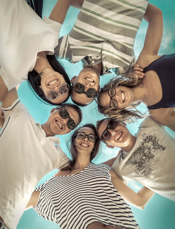 young group: Group of friends on the beach under sunlight. Stock Photo