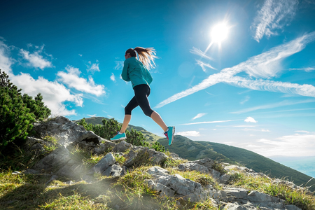 recreational: Female running in mountains under sunlight. Stock Photo