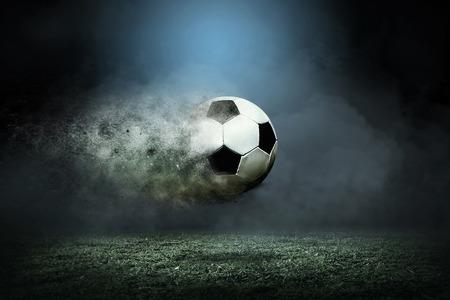 balon soccer: Moviendo el balón de fútbol alrededor de las gotas del chapoteo en el campo del estadio.