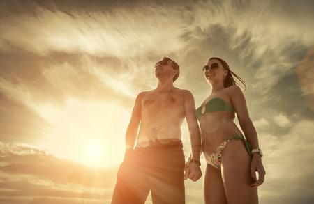 sunlight sky: Couple stay on the beach under sky with sunlight.