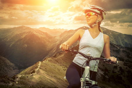 people in action: Beautiful woman in helmet and glasses stay on the bicycle around mountains.