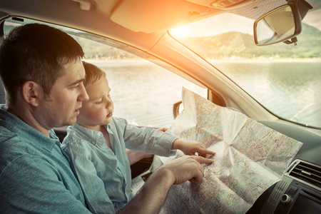 Father and son looking on map in car Stock Photo - 61288666