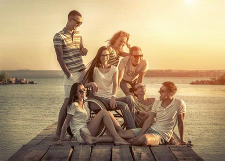 Happiness friends on pier under sunset light.