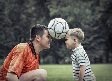 football play: Father and son playing football in park at sunny day