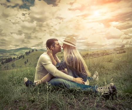 pareja de esposos: La felicidad pareja sentada en la hierba verde en el tiempo de día soleado