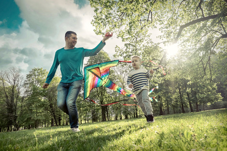 Runnings little boy and father flies with them kite in the park under sunligt. Zdjęcie Seryjne