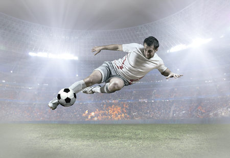 jumps: Soccer player with ball in action on field of stadium