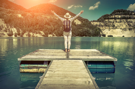 one person: Woman stay on pier, mountains lake at sunday time. Stock Photo
