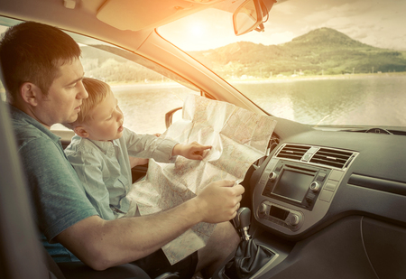 Father and son looking on map in car Stock Photo