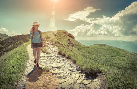 mochila de viaje: Woman hiking in mountains at sunny day time.