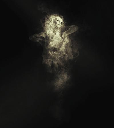 Danseuse de la fumée sur le fond sombre