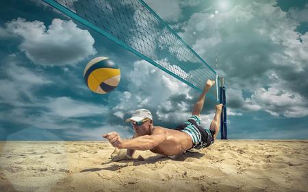Hráč plážového volejbalu v akci na slunečný den pod modrou oblohou.