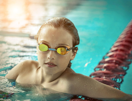 Swimmer child. Portrait of swimming child athlete with goggles after training in waterpool. Stock Photo