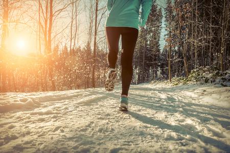 vitality: Woman Running at snowly winter under sunlight.
