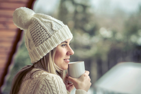 winter weather: Female in white with cup of coffee at the winter weather