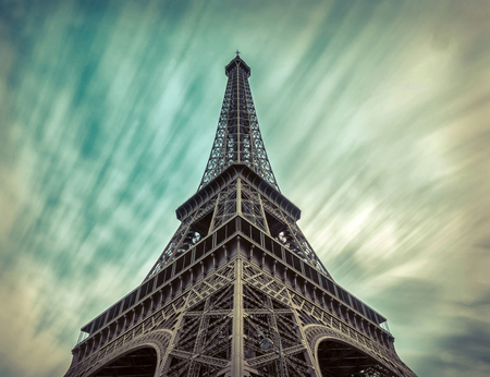 Eiffel Tower under motions clouds. Beautiful view on one of famous popular place in Paris with long exposition. Stock Photo